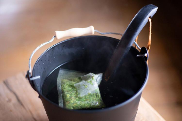 Nystad Sauna infusing herbs in a sauna bucket